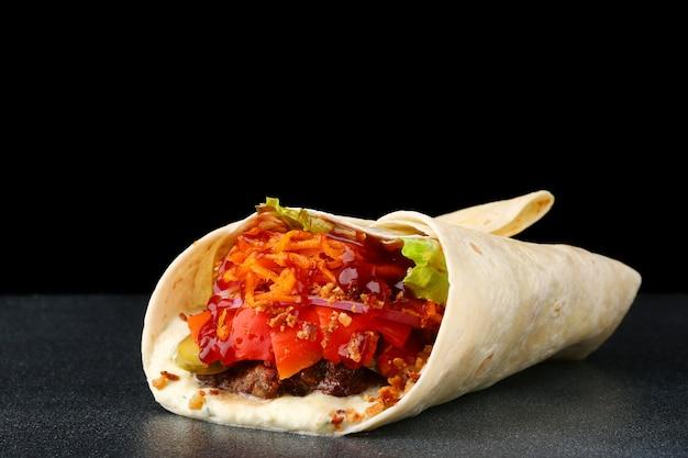 牛肉と野菜の分離の黒い背景においしいブリトーをラップします。ブリトー、伝統的なメキシコ料理。
