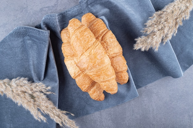 Tasty buttery croissants over grey background.
