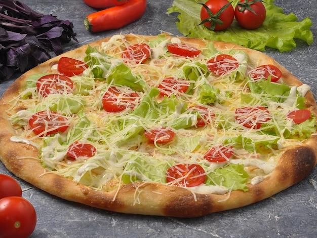 野菜で飾られた灰色の背景においしいシーザーピザ