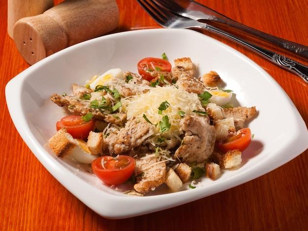 Вкусный салат цезарь с курицей в белой тарелке на деревянном столе