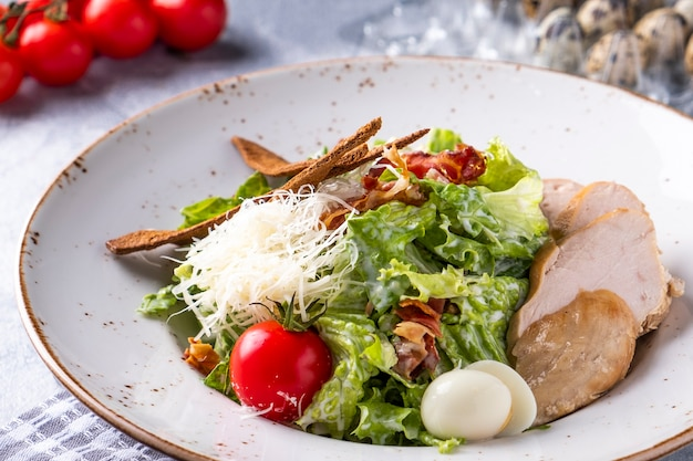 Tasty caesar salad with chicken on a plate.