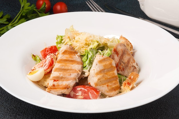 Tasty caesar salad with chicken on a white plate on a black background