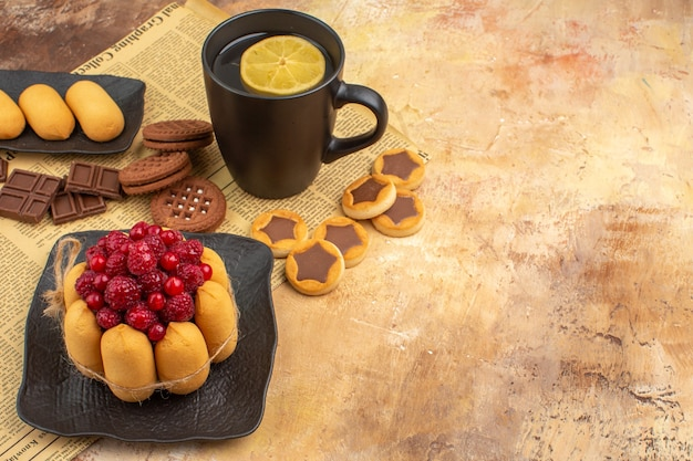 혼합 색상 테이블에 검은 컵에 맛있는 케이크 다른 비스킷과 차