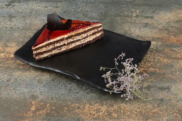 大理石の表面に花が付いた皿の上のおいしいケーキ