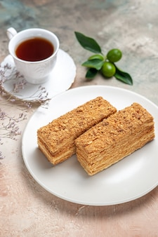 Вкусные кусочки торта с чаем на сером