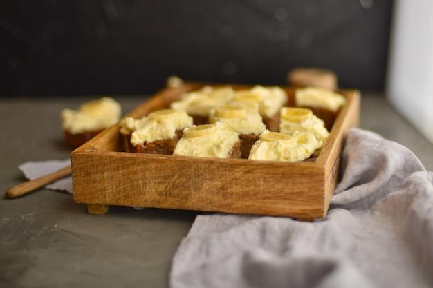 나무 상자에 크림과 함께 바나나와 맛있는 케이크. 테이블에 치즈 케이크입니다. 달콤한 토피 케이크.
