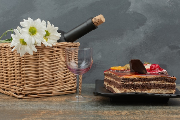 Tasty cake with basket and bottle on marble table.