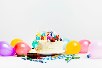 Tasty cake with berries and happy birthday title near colourful balloons