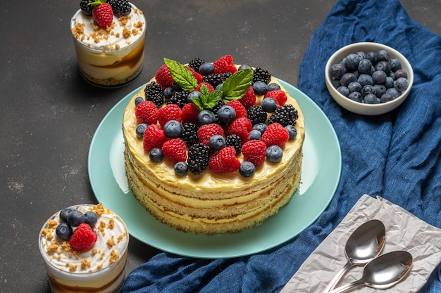 Вкусный торт со свежими ягодами и сладкими десертами на черном фоне.