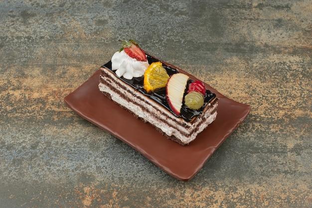 Gustosa torta con frutta sulla piastra su sfondo marmo. foto di alta qualità