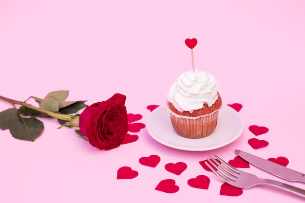 Tasty cake with whip between decorative hearts near flower
