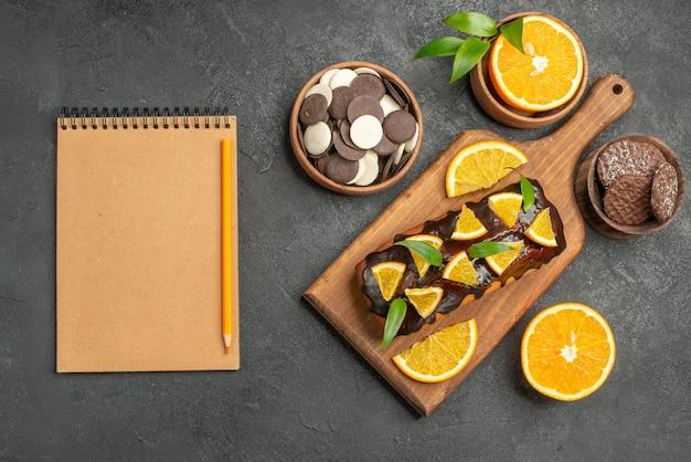 맛있는 케이크는 어두운 테이블에 커팅 보드에 노트북 옆에 비스킷으로 오렌지를 자릅니다.
