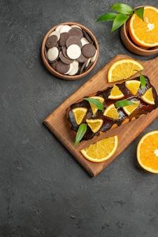 맛있는 케이크는 어두운 테이블에 커팅 보드에 비스킷으로 오렌지를 자릅니다.