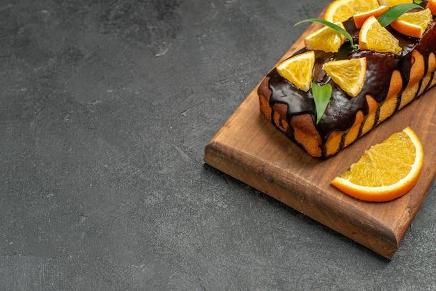 Вкусные торты, украшенные апельсинами и шоколадом на разделочной доске на черном столе