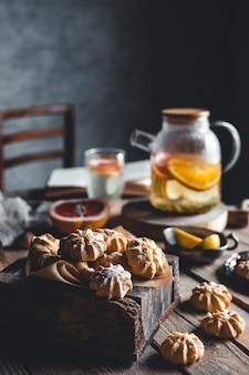 木製のタブレットに新鮮なグレープフルーツのスライスと熱いお茶でおいしいケーキ。ヘルシードリンク、エコ、ビーガン