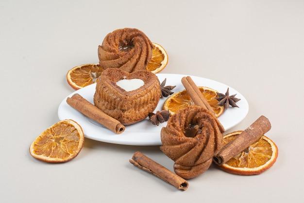 白いプレートにオレンジスライス、クローブ、シナモンのおいしいケーキ