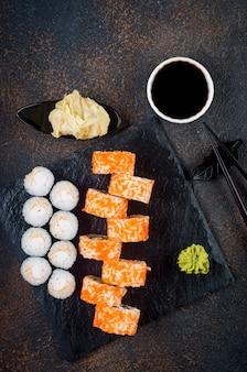 おいしいカリフォルニアロールと巻き寿司を石皿にのせ、ソース、箸、生姜、わさび
