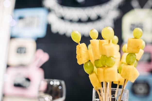 Gustose tartine con formaggio e uva verde in vetro alla festa su sfondo sfocato. snack per feste e concetto di cibo.