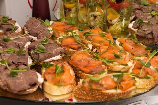 뷔페에서 연어와 쇠고기를 곁들인 맛있는 카나페