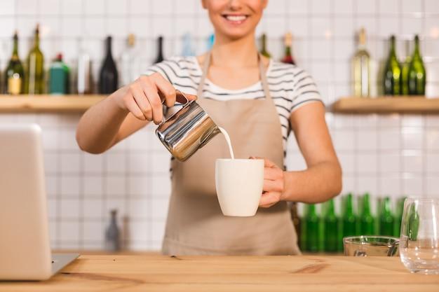 おいしいカプチーノ。ミルクを追加しながら楽しい素敵な女性によって保持されているコーヒーとカップの選択的な焦点