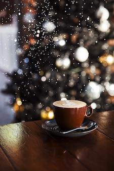 クリスマスツリーと雪にいくつかのぼやけたライトとおいしいカプチーノ。休日のコンセプト。