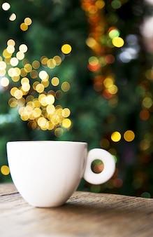 クリスマスツリーの休日のコンセプトにいくつかのぼやけたライトとおいしいカプチーノ