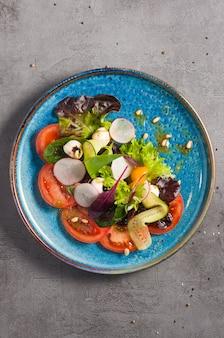Вкусный салат капрезе на сером фоне. вид сверху