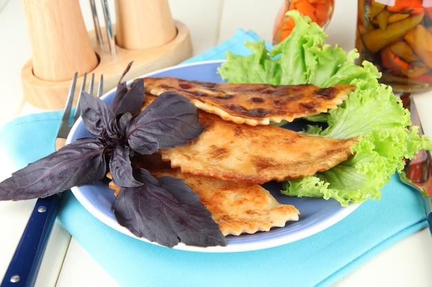 Вкусные чебуреки со свежей зеленью на тарелке на деревянном столе