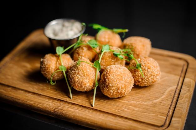 Вкусные сырные шарики, украшенные зеленью и соусом, подаются на деревянной тарелке