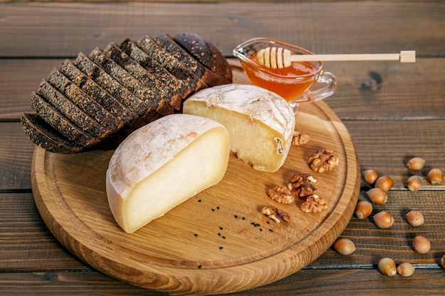 Tasty cheese, honey, bread and nuts. concept of healthy food