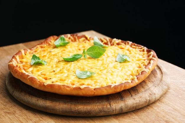 Вкусная сырная пицца с базиликом на черной поверхности