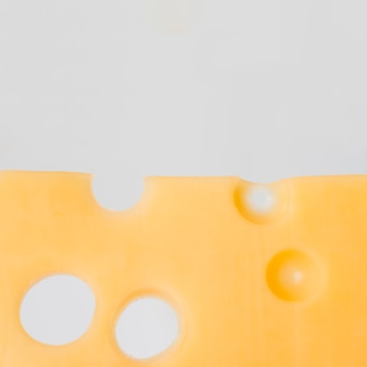Tasty cheese with holes on whiteboard
