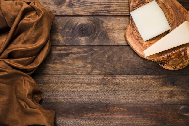 Tasty cheese on wooden cheese board with brown silk fabric over old wooden surface