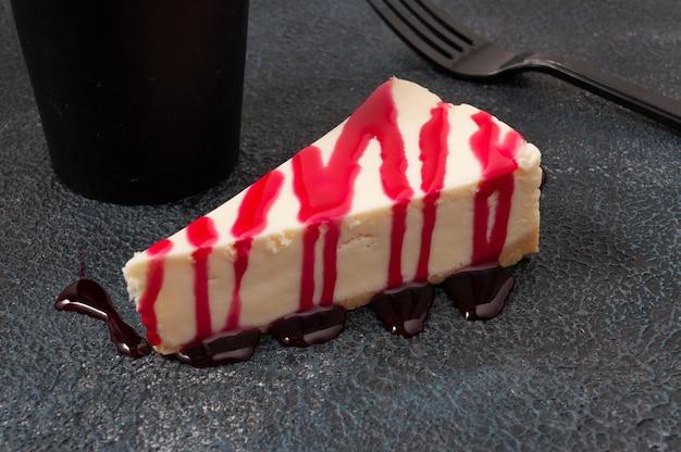 Вкусный чизкейк с ягодным соусом на темном фоне