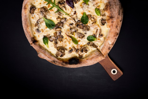 Tasty cheesy mushroom pizza and basil leaves on wooden board over black backdrop