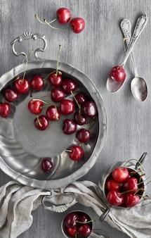 Вкусная вишня в старинных металлических пластинах, вид сверху на текстурированном фоне