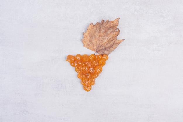 Gustosa marmellata di ciliegie con foglia sul tavolo bianco.