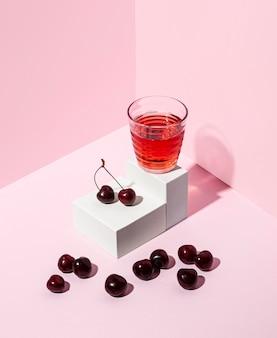ピンクの背景を持つおいしいチェリージュース