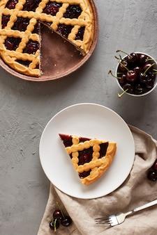 Вкусный вишневый пирог на бетонном столе. плоская планировка, вид сверху.