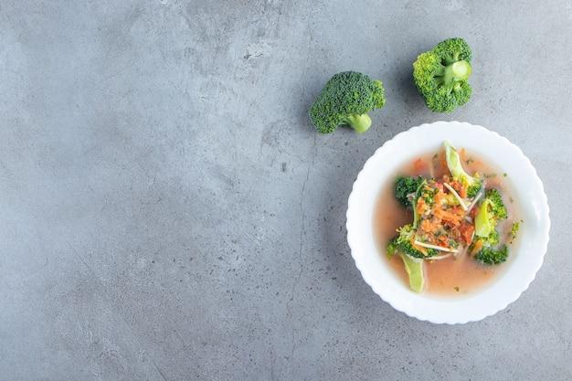 Вкусный куриный суп в миске на мраморном фоне.