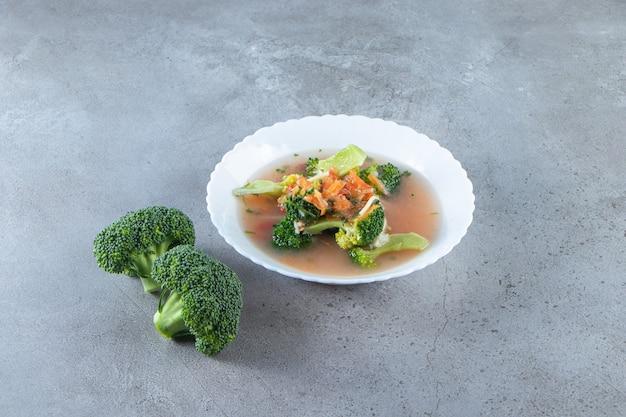 Вкусный куриный суп в миске на мраморной поверхности.