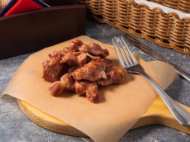 Вкусные куриные желудки, приготовленные в копченом виде на деревянной доске