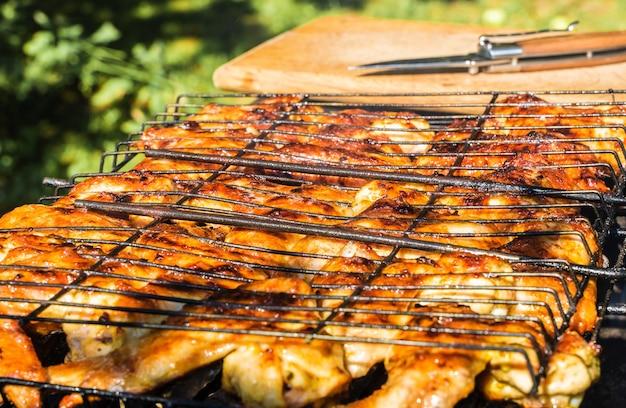 夏のバーベキューで焼くおいしい手羽先。鶏肉の美味しい一片。ストックフォトを閉じます。