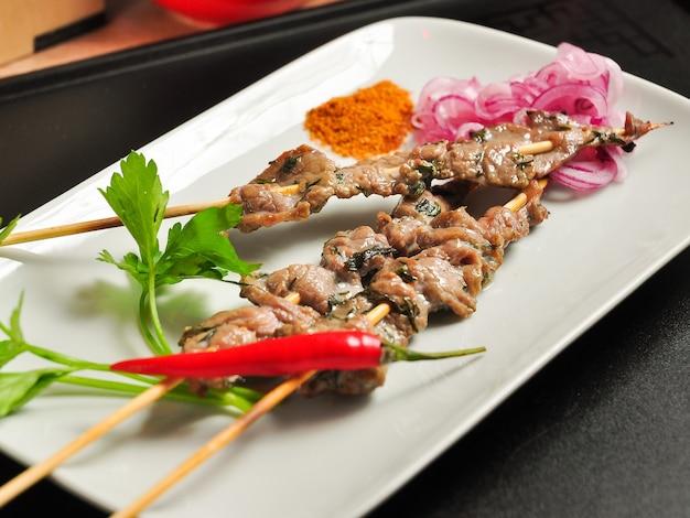 Вкусный шашлык из китайской говядины на белой тарелке
