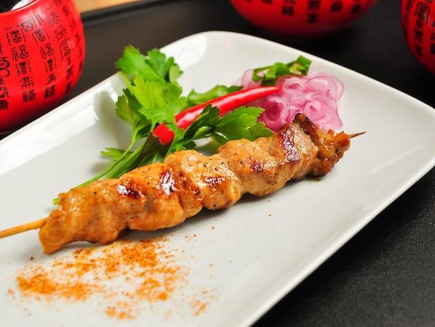흰색 접시에 맛있는 중국 닭 꼬치