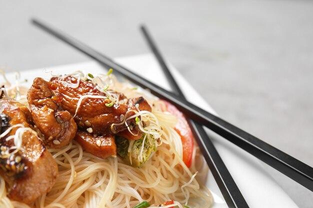 Вкусная китайская лапша с мясом на тарелке, крупным планом