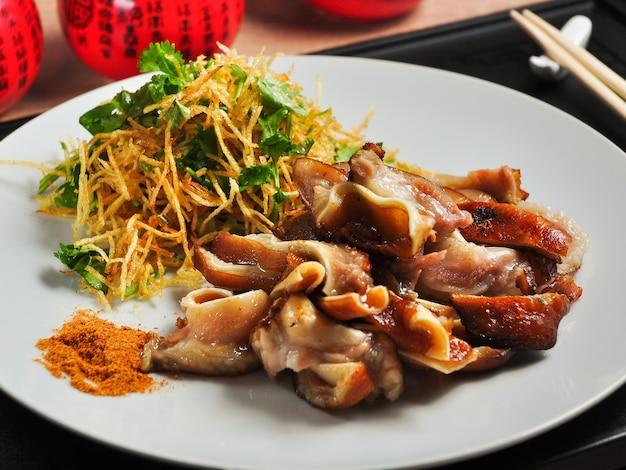 야채와 감자 튀김의 얇은 빨대와 함께 맛있는 중국 돼지 귀