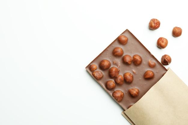 Вкусная плитка шоколада в бумаге на белом