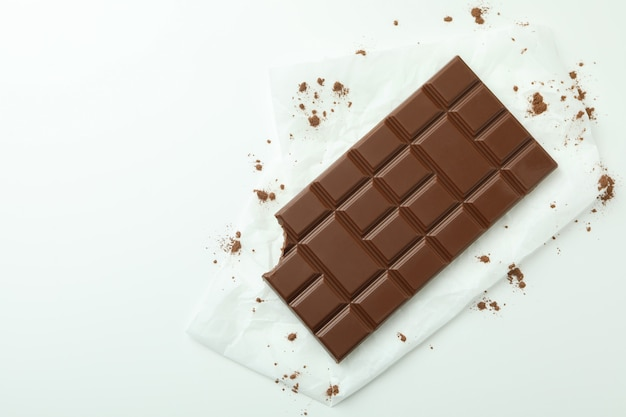 Tasty chocolate bar on paper on white background