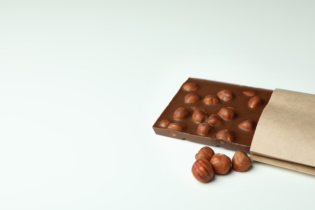 Tasty chocolate bar in paper on white background